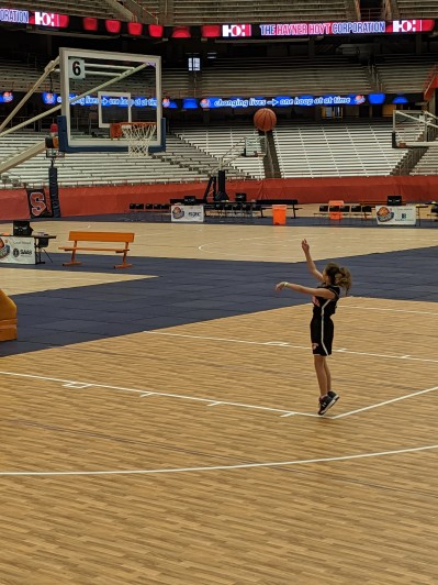 Bean shooting baskets in an empty arena.
