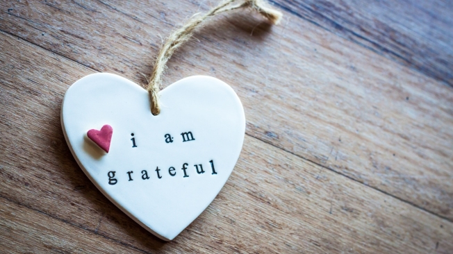 "A white heart ornament is on a wooden surface. On the heart, it has a small pink heart and the words ""I am grateful""."